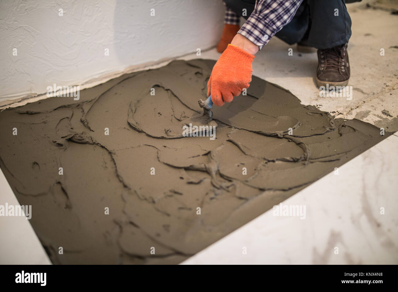 Laying ceramic tiles troweling mortar onto a concrete floor in laying ceramic tiles troweling mortar onto a concrete floor in preparation for laying floor tile dailygadgetfo Images