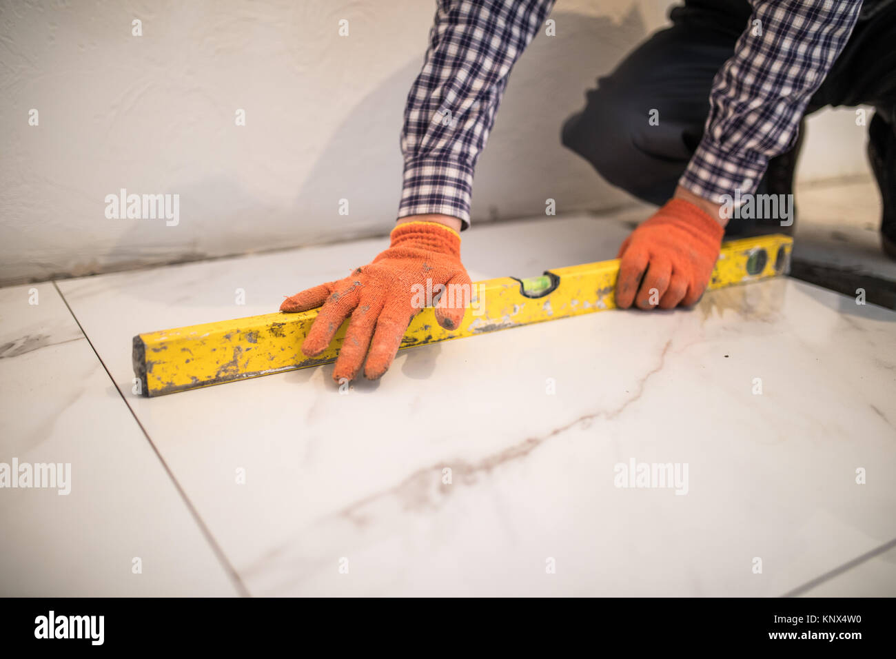 Renovation professional tile improvement handyman stock photos home tile improvement handyman with level laying down tile floor stock image dailygadgetfo Choice Image