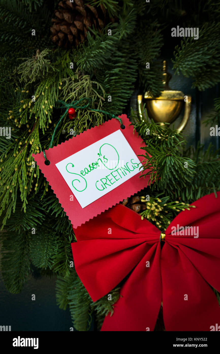 Seasons greetings stock photos seasons greetings stock images alamy christmas wreath on door with red bow and seasons greetings message kristyandbryce Images