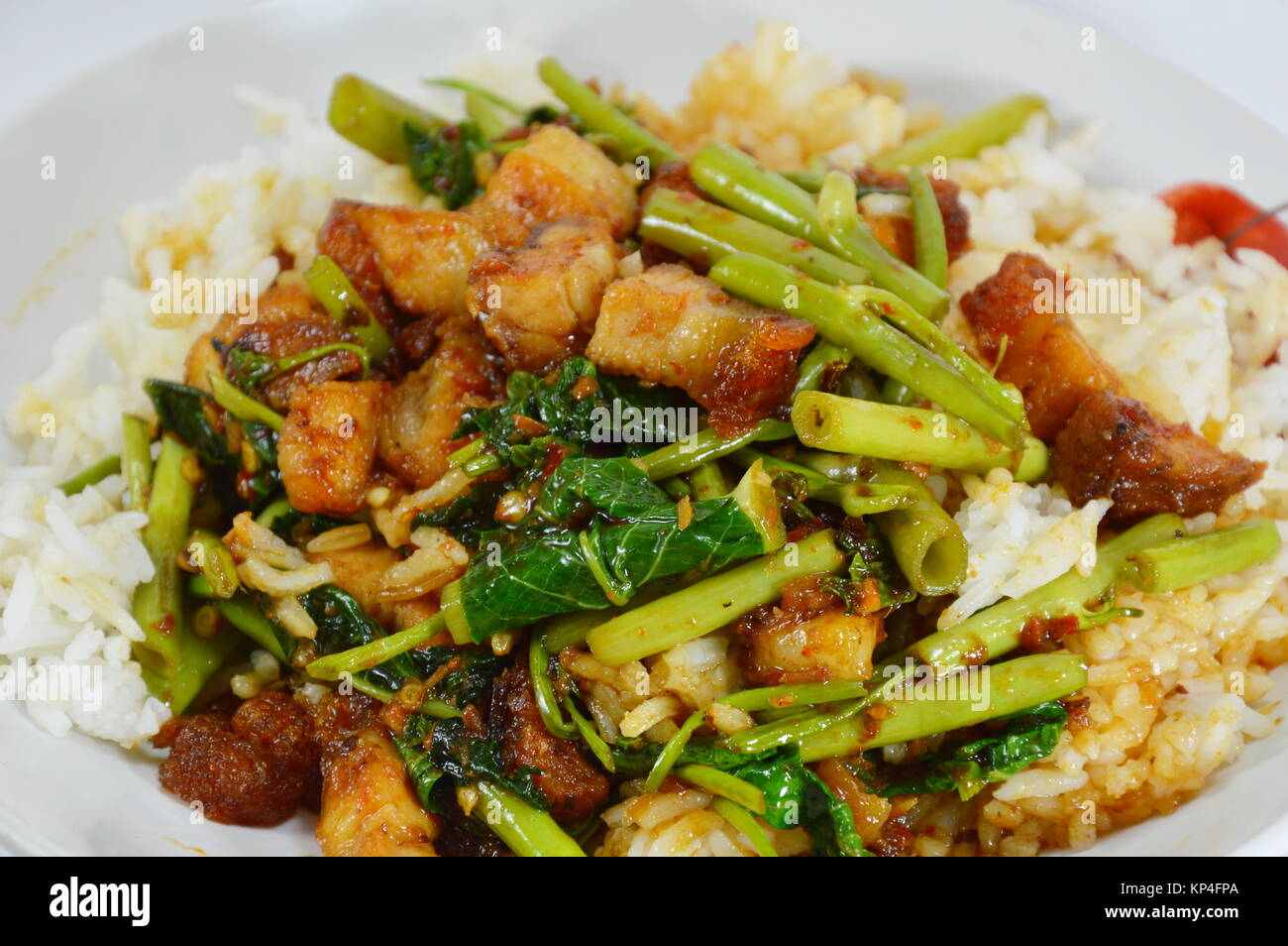 stir fried morning glory with crispy pork curry topping on