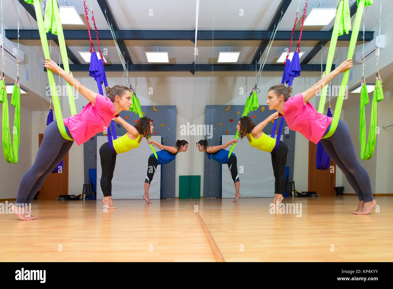 three pretty girls practice anti gravity yoga position in gym on hammocks   doing exercises meditating in calm position on a aerial yoga class in fr three pretty girls practice anti gravity yoga position in gym on      rh   alamy