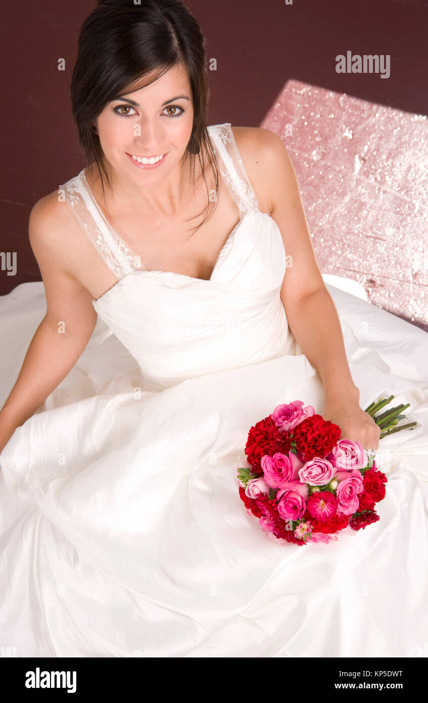 Bride Sitting In White Wedding Dress With Flower Bouquet Red Roses