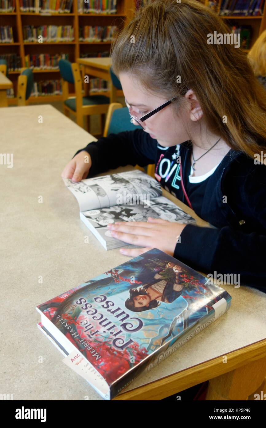 6th Grade Girl Looking At Book In Library Wellsville New York Usa