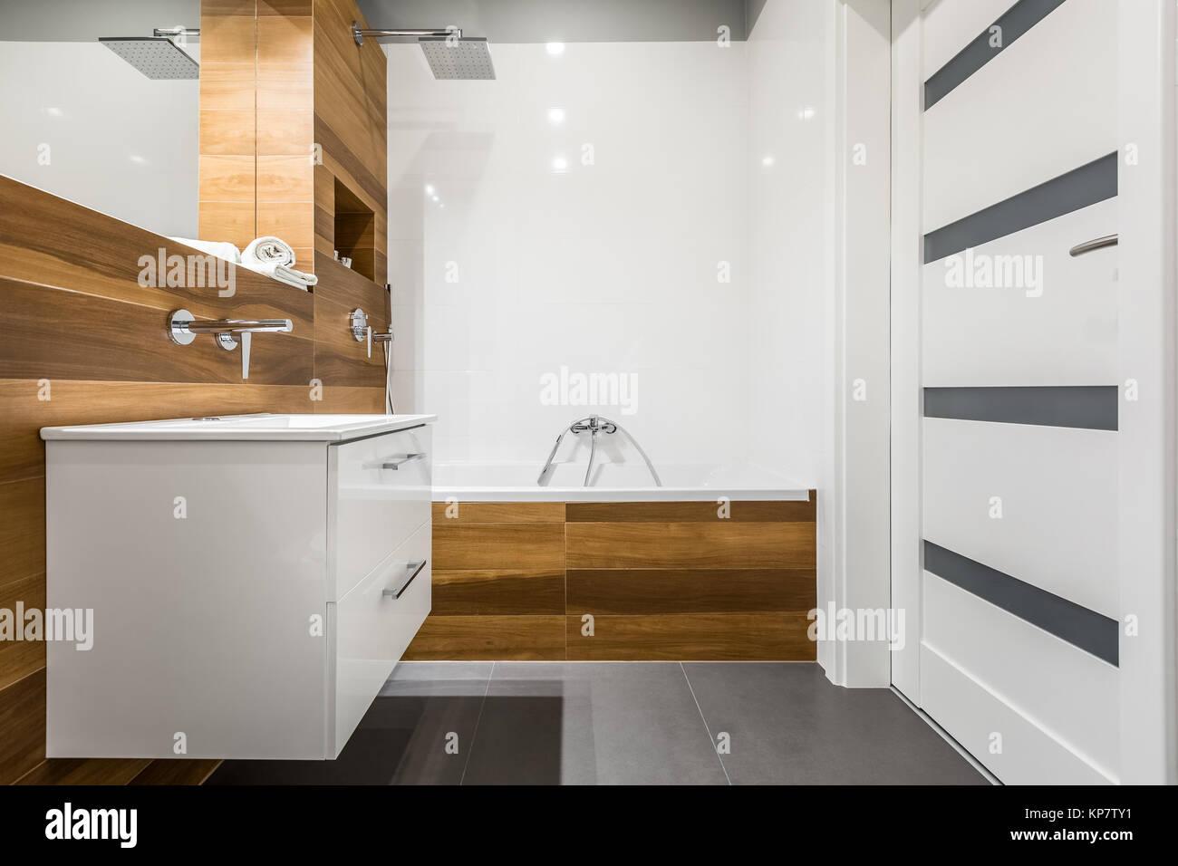 Modern bathroom with wooden tiles, white door and concrete floor ...
