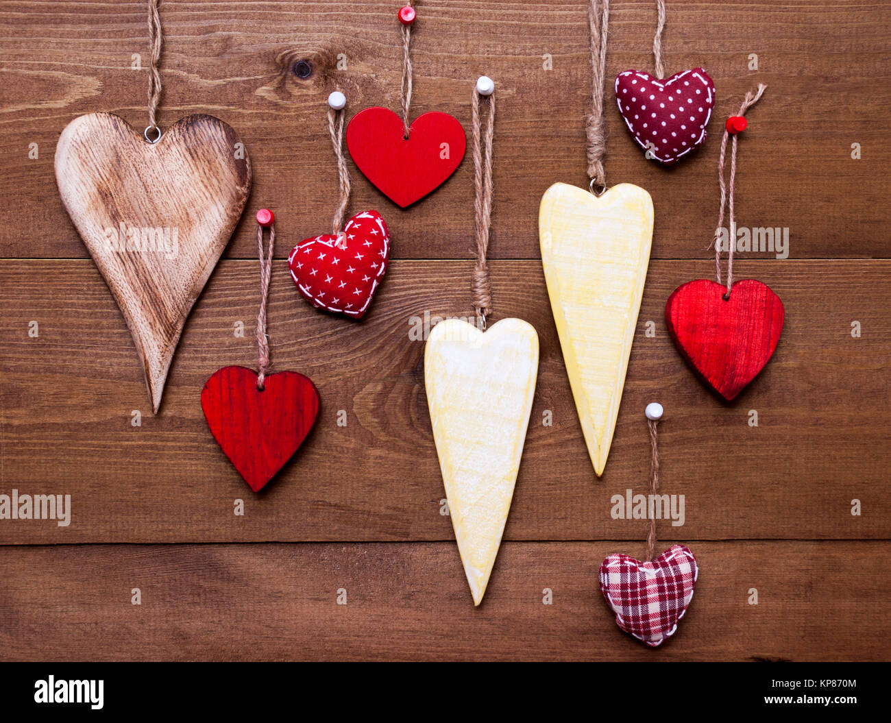 Many Red And Yellow Hearts Hanging Infront Of Wooden Background
