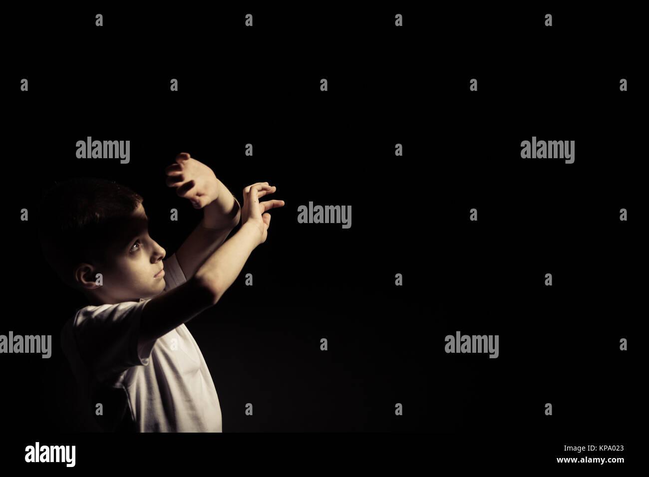 divine lighting. Boy Looking Up While Covering Light Against Black - Stock Image Divine Lighting