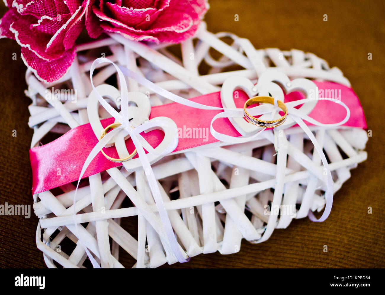 white wooden heart-shaped pillow with flowers and pink ribbons for ...
