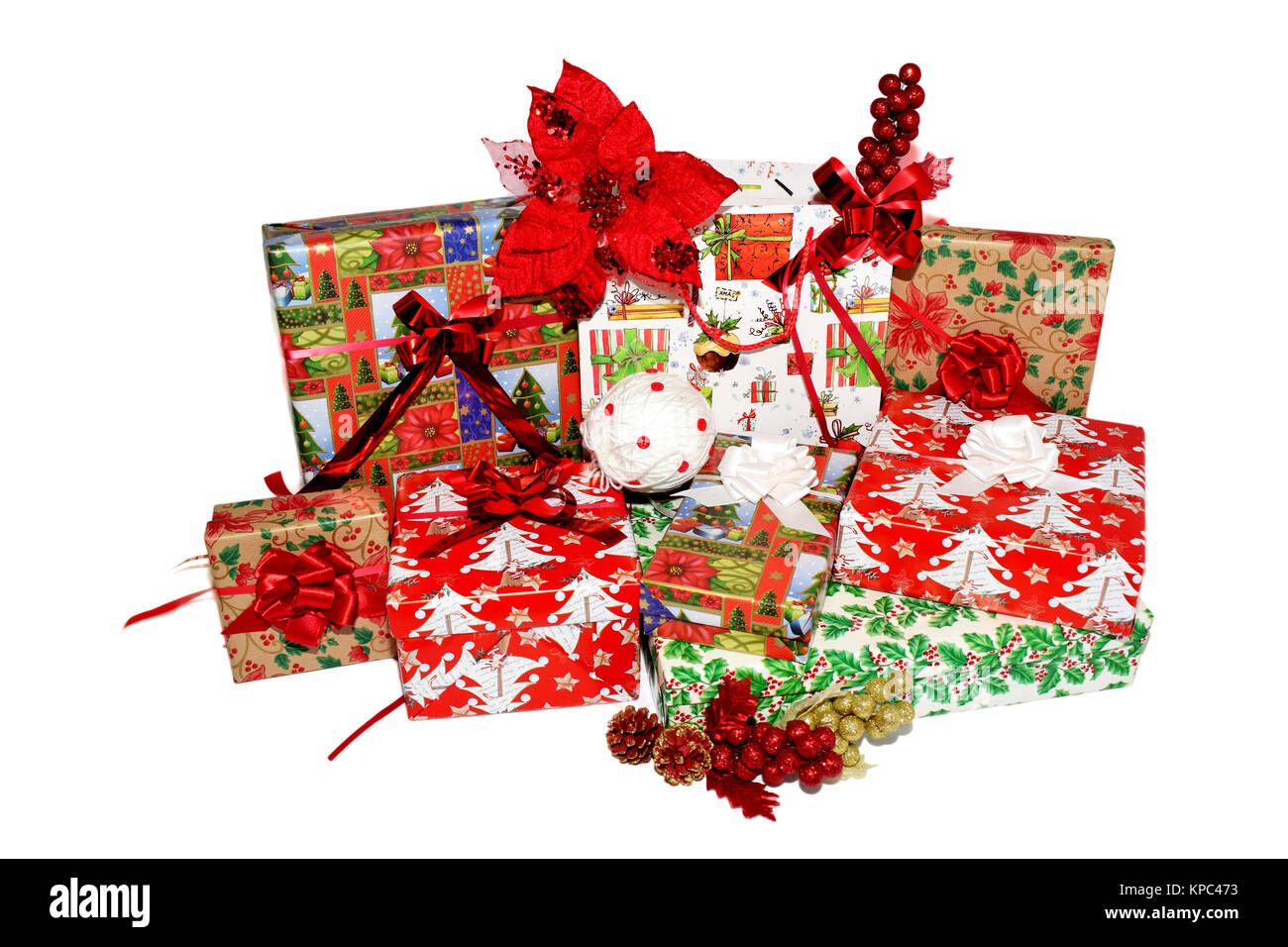 christmas gifts in boxes and bags wrapped in themed paper decorations with red decorative flowers christmas white and golden globes and pine cones