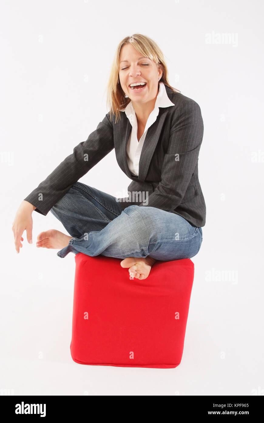 lachende frau 25 sitzt auf einem roten stoffwuerfel young blond woman - Rosa Krbislampe