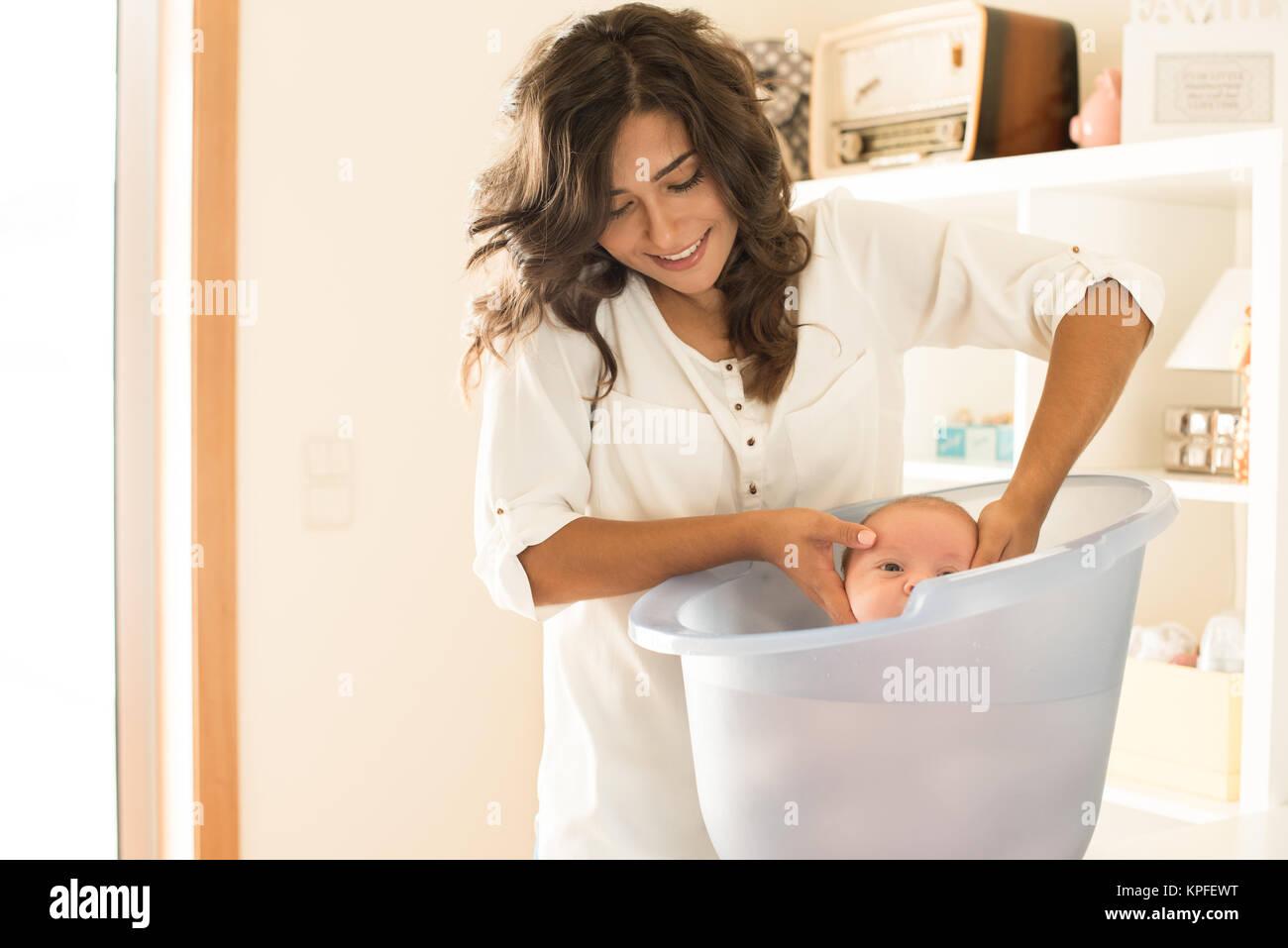 Mother washing a newborn baby in a bath tub Stock Photo: 168756724 ...