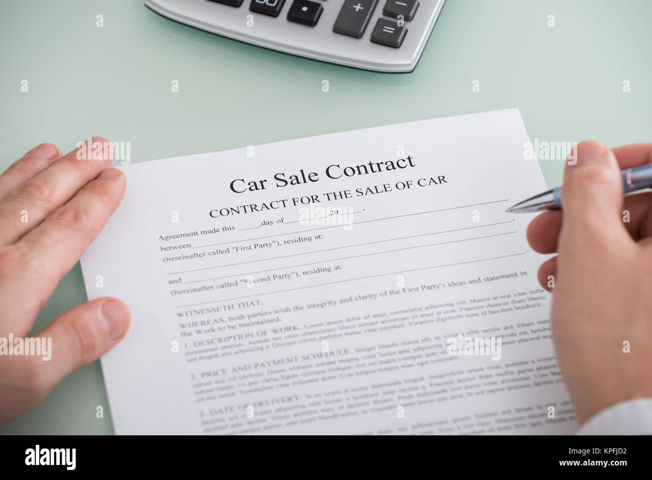 person filling car sale contract form