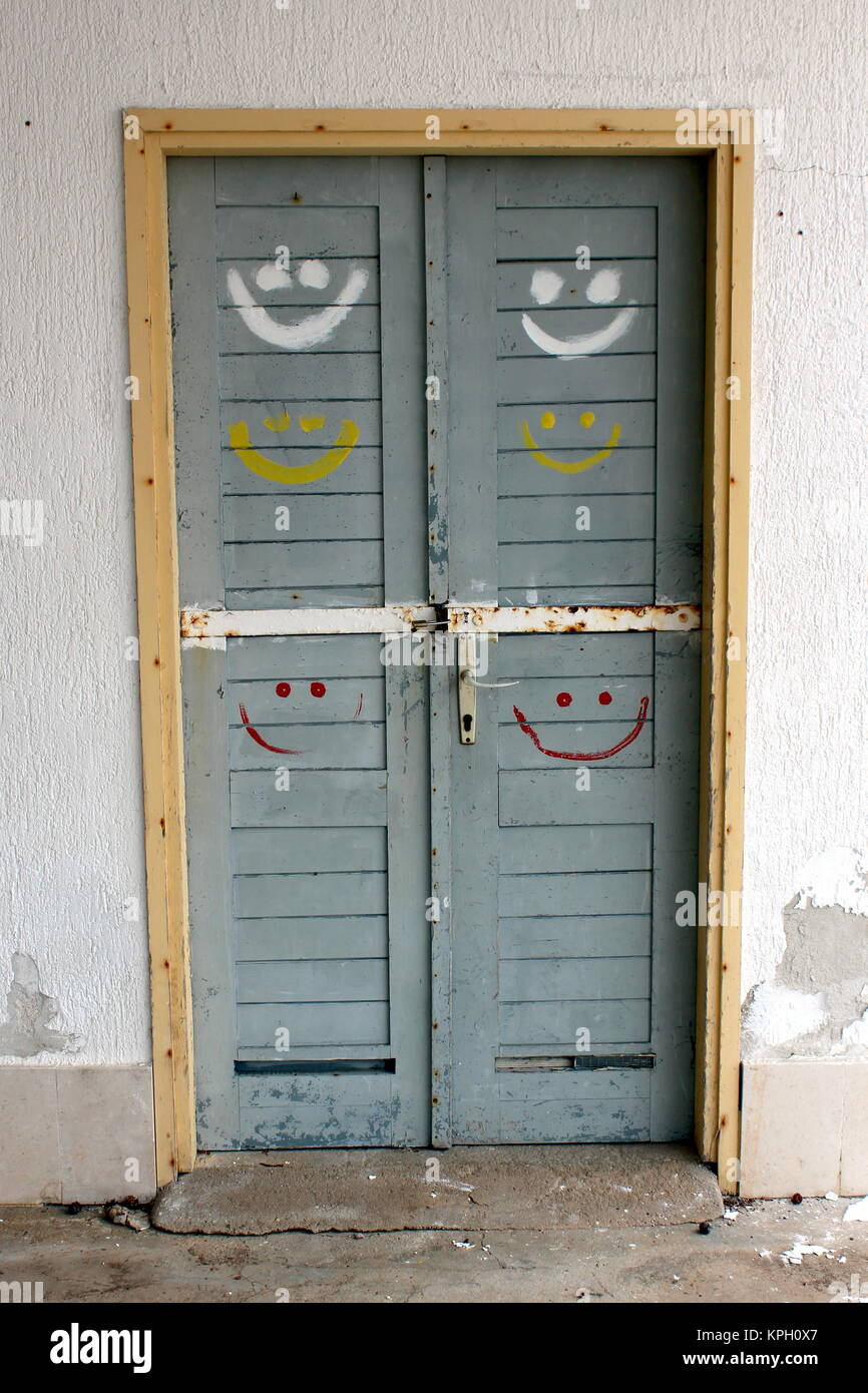 Rustic old light blue doors in yellow wooden frame locked with strong metal bar and padlock with six smileys painted in red white and yellow color & Rustic old light blue doors in yellow wooden frame locked with ...