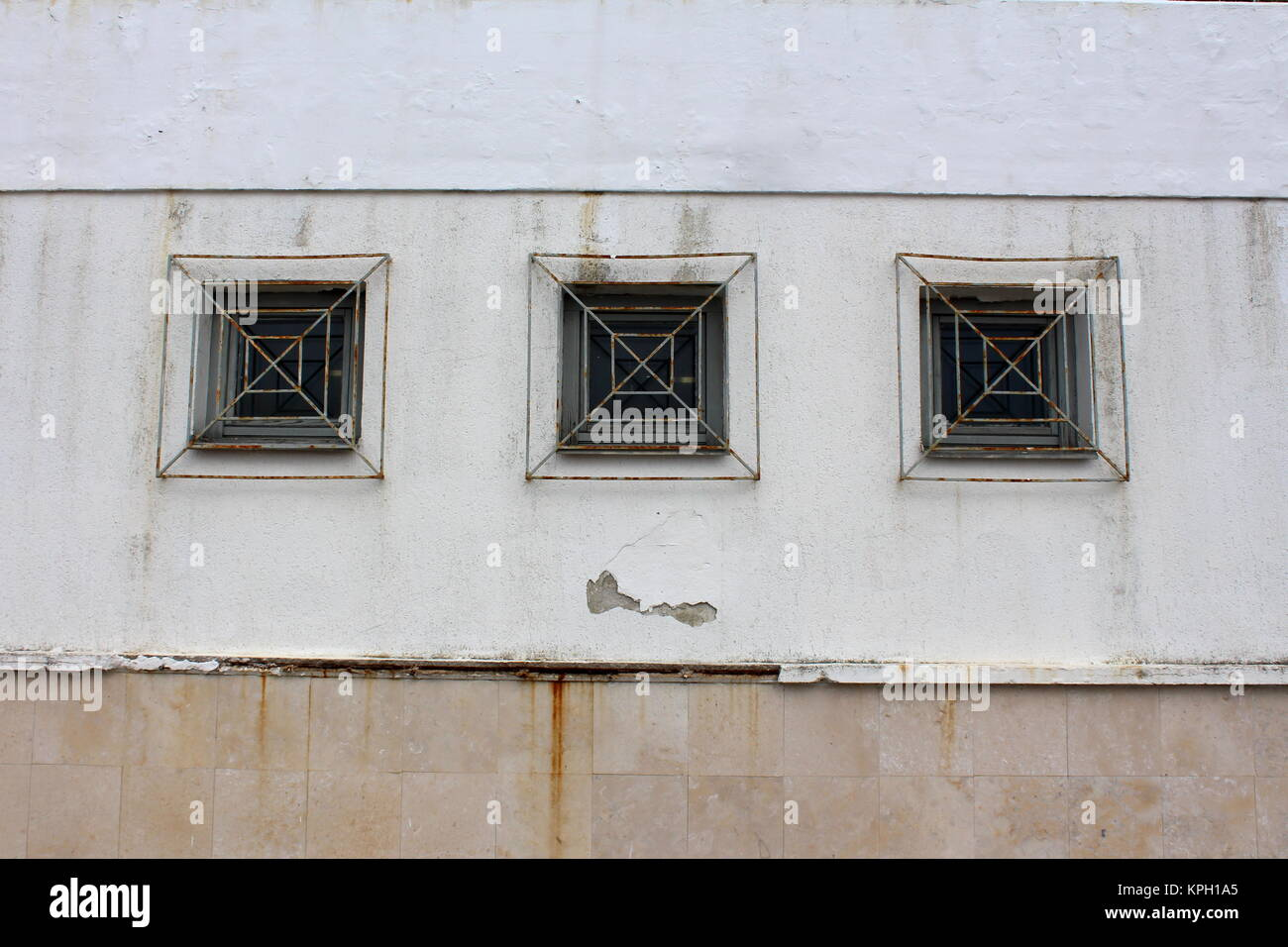 three wooden frame rectangle glass windows with partially rusted metal bars mounted on dilapidated wall outside - Metal Frame Windows