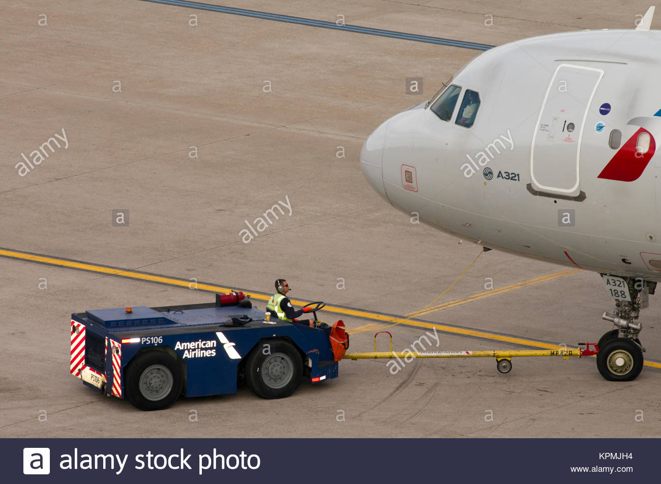 an aircraft push back tractor pushes a jet airplane away from the
