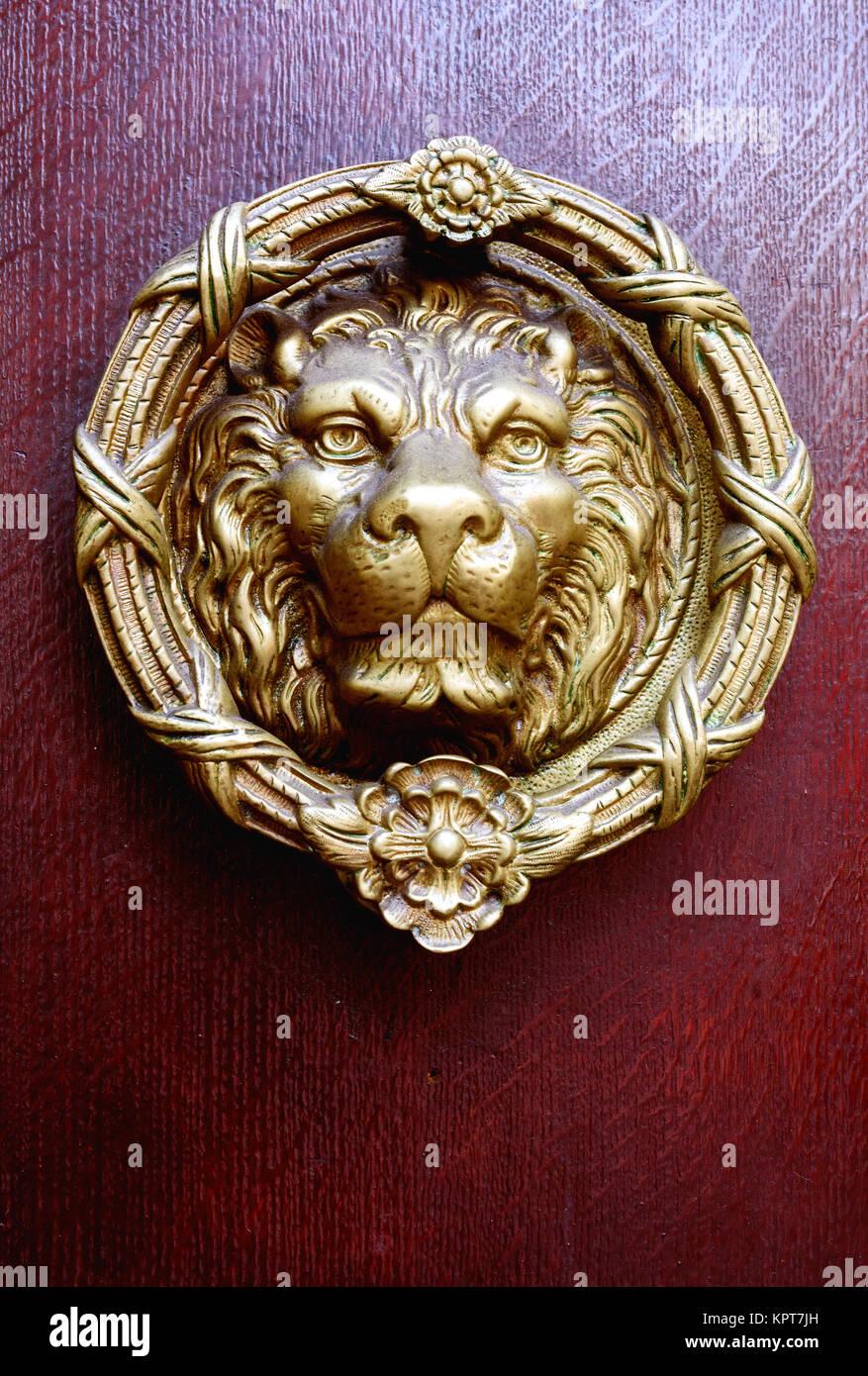 Single Golden Coloured Brass Lions Head Door Knocker And Vintage Antique  Wooden Door In Dark Burgundy Red