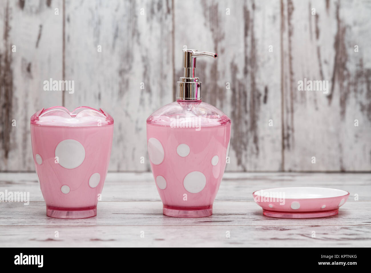 Set Of Cute Pink Bathroom Accessories On White Wooden Background