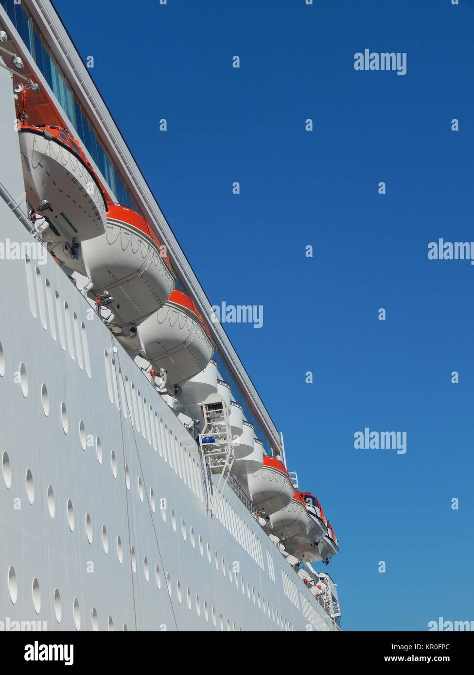 Side View Port Of A Big White Cruise Ship With Lifeboats Stock - Port side of a cruise ship