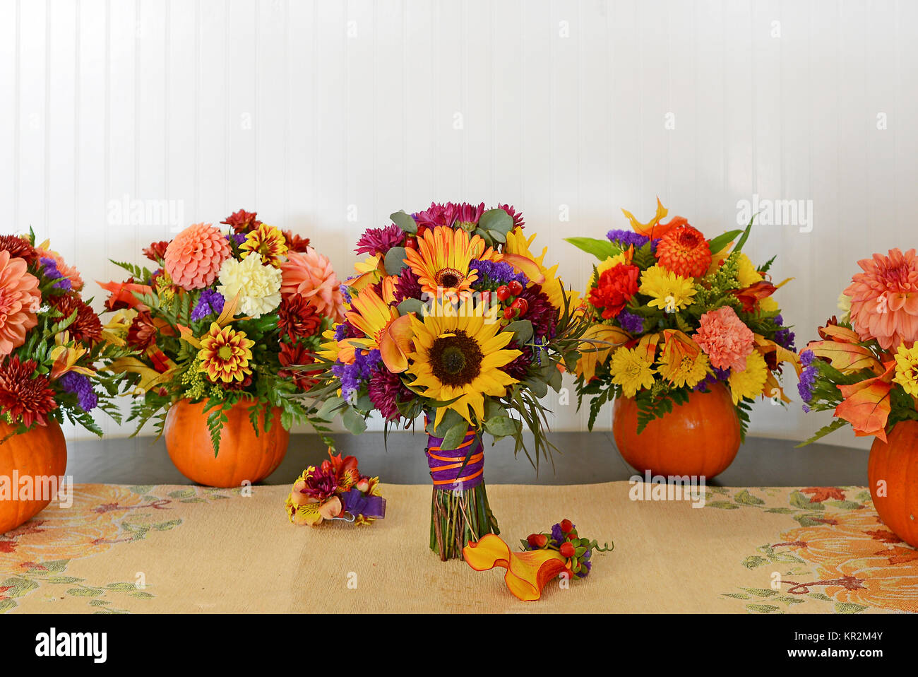 Photo of fall wedding flowers the sunflower bridal bouquet is stock photo of fall wedding flowers the sunflower bridal bouquet is surrounded by centerpieces of fresh flowers in real pumpkins colorful and fun izmirmasajfo