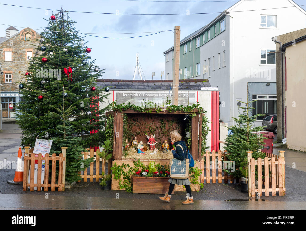 Christmas tree and nativity scene with lady walking past in Stock ...