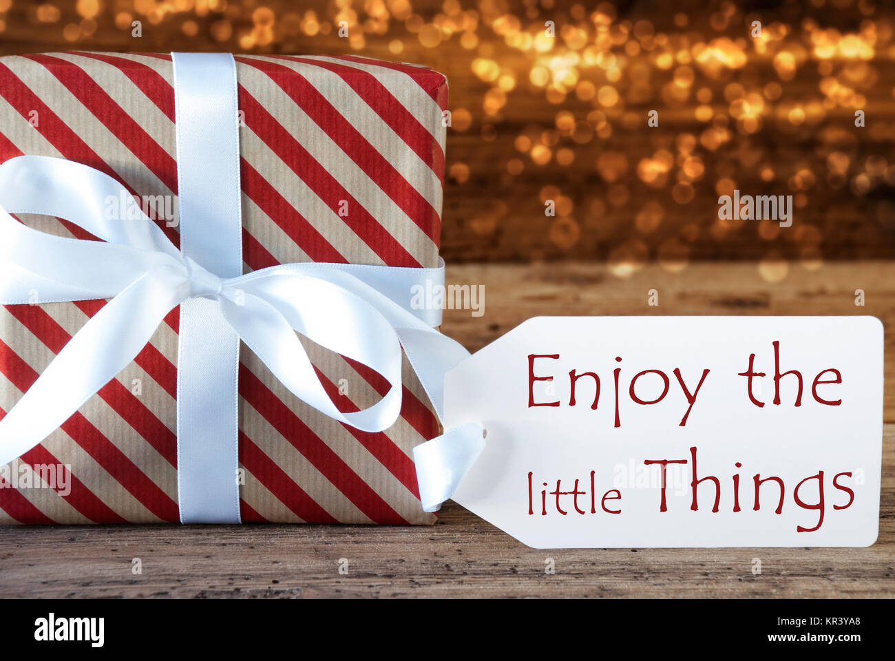 Macro of christmas gift or present on atmospheric wooden background card for seasons greetings best wishes or congratulations white ribbon with bow english quote enjoy the little things m4hsunfo
