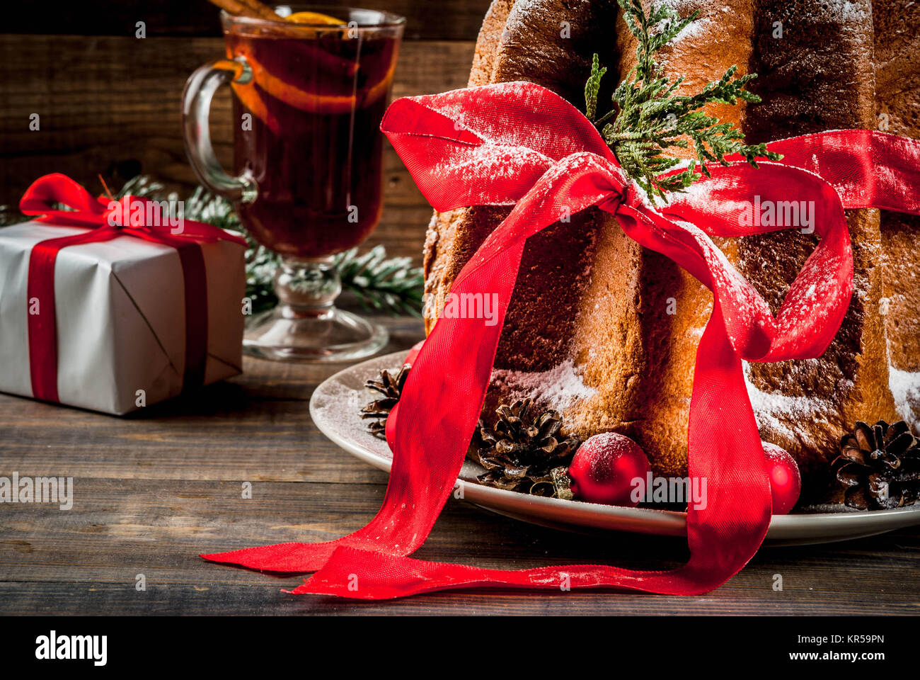 traditional italian christmas fruit cake panettone pandoro with festive red ribbon and christmas decorations gift box and mulled wine on wooden home
