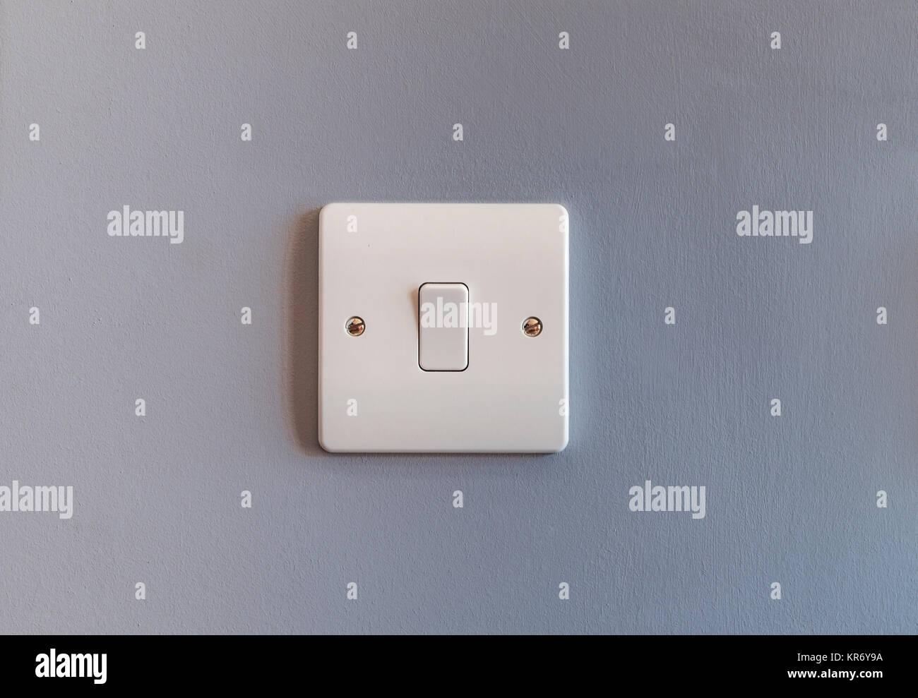 UK domestic single light switch in white plastic on a grey coloured ...