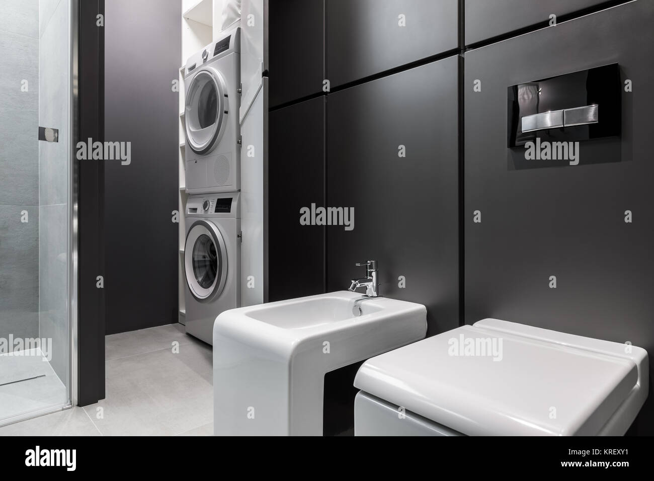 Laundry Space With Washing Machine And Dryer In Modern Bathroom