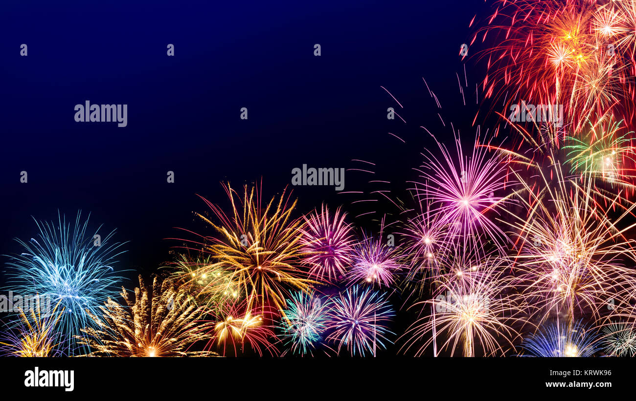 multi colored fireworks as a border on dark blue background ideal for new year or other celebration events