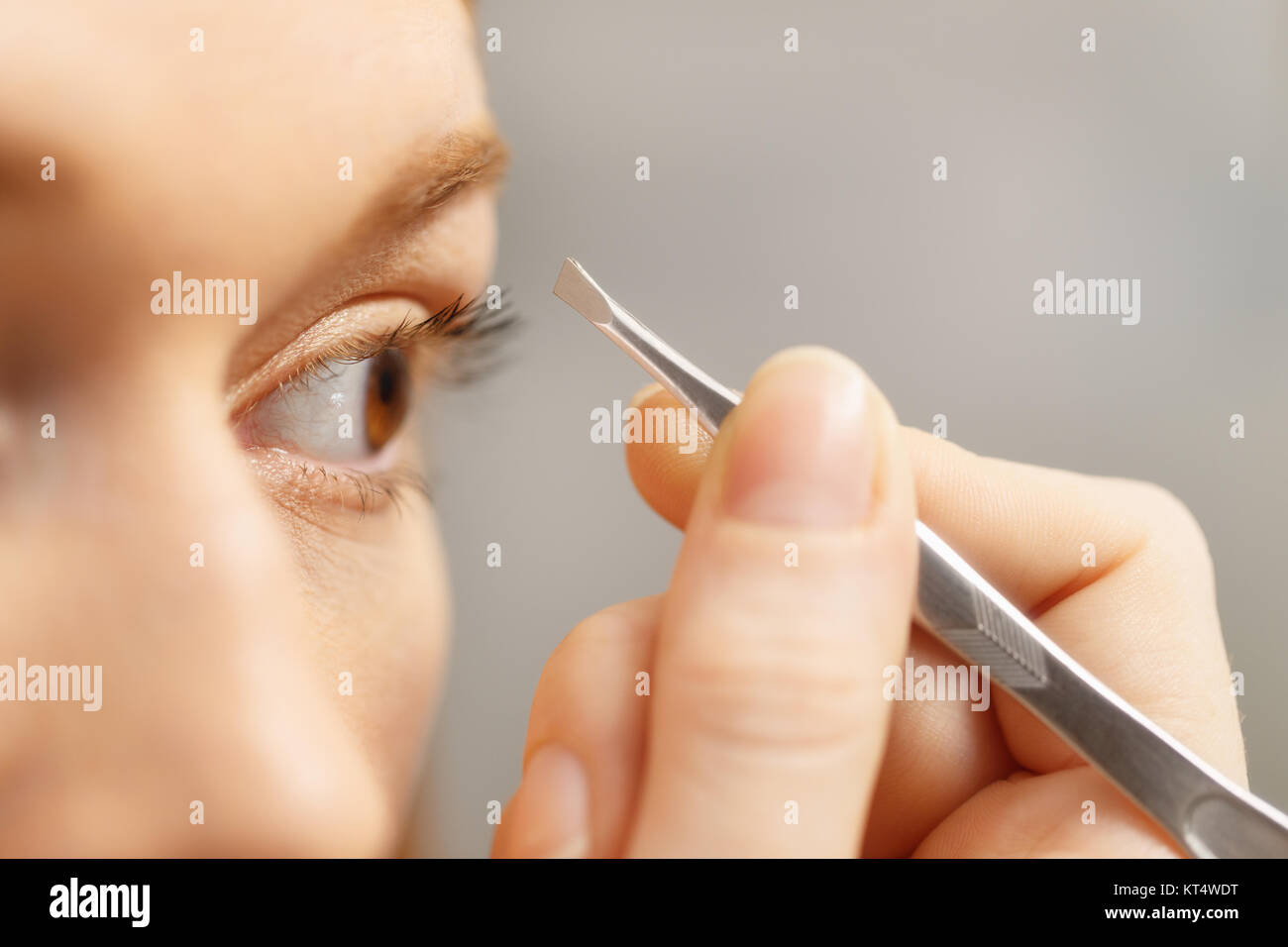 Girl Pulling Eyebrows With Tweezers Young Woman Looking At Mirror