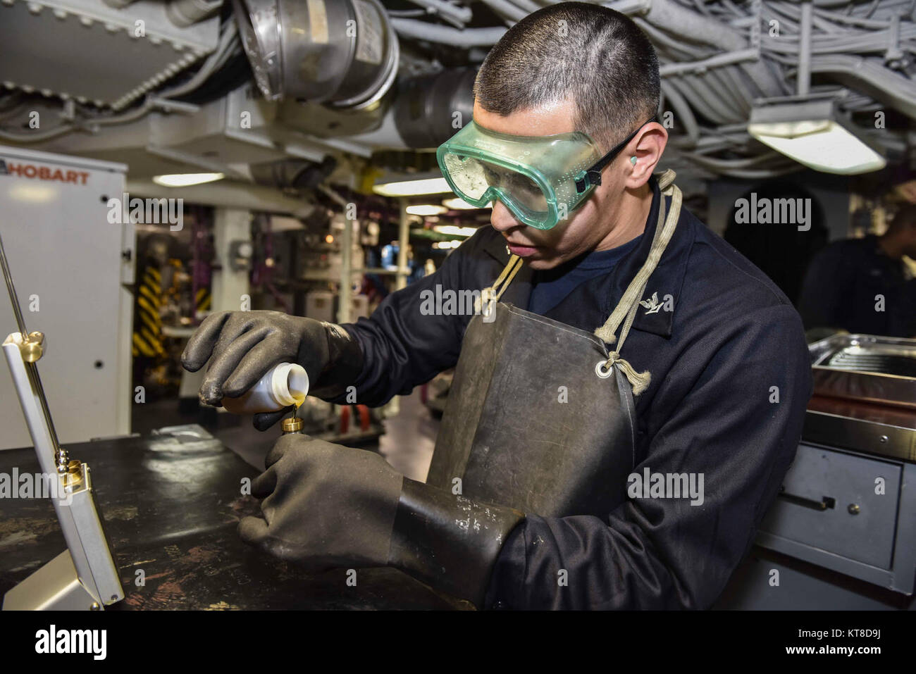 engineman 3rd class angelo torres tests a lube oil sample aboard the