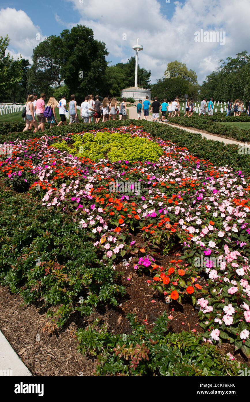 Flowers bloom in a garden near the Memorial Amphitheater and the USS ...