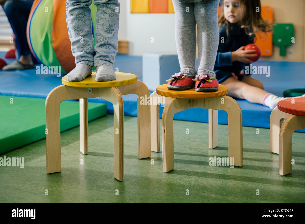 Feet of two children standing on chairs of different heights in kindergarten  sc 1 st  Alamy & Feet of two children standing on chairs of different heights in ...