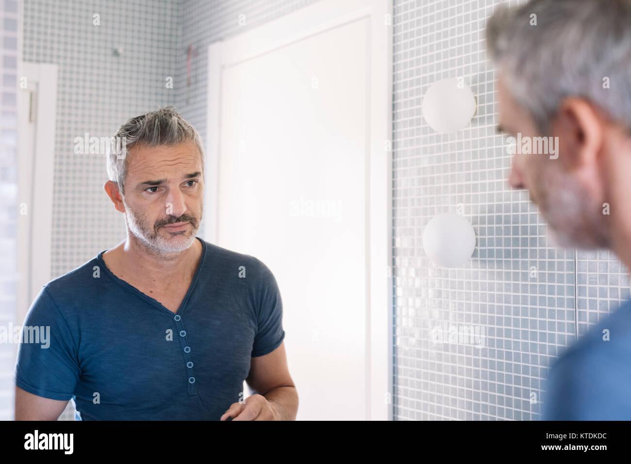mature man looking in bathroom mirror stock photo 169945704 alamy