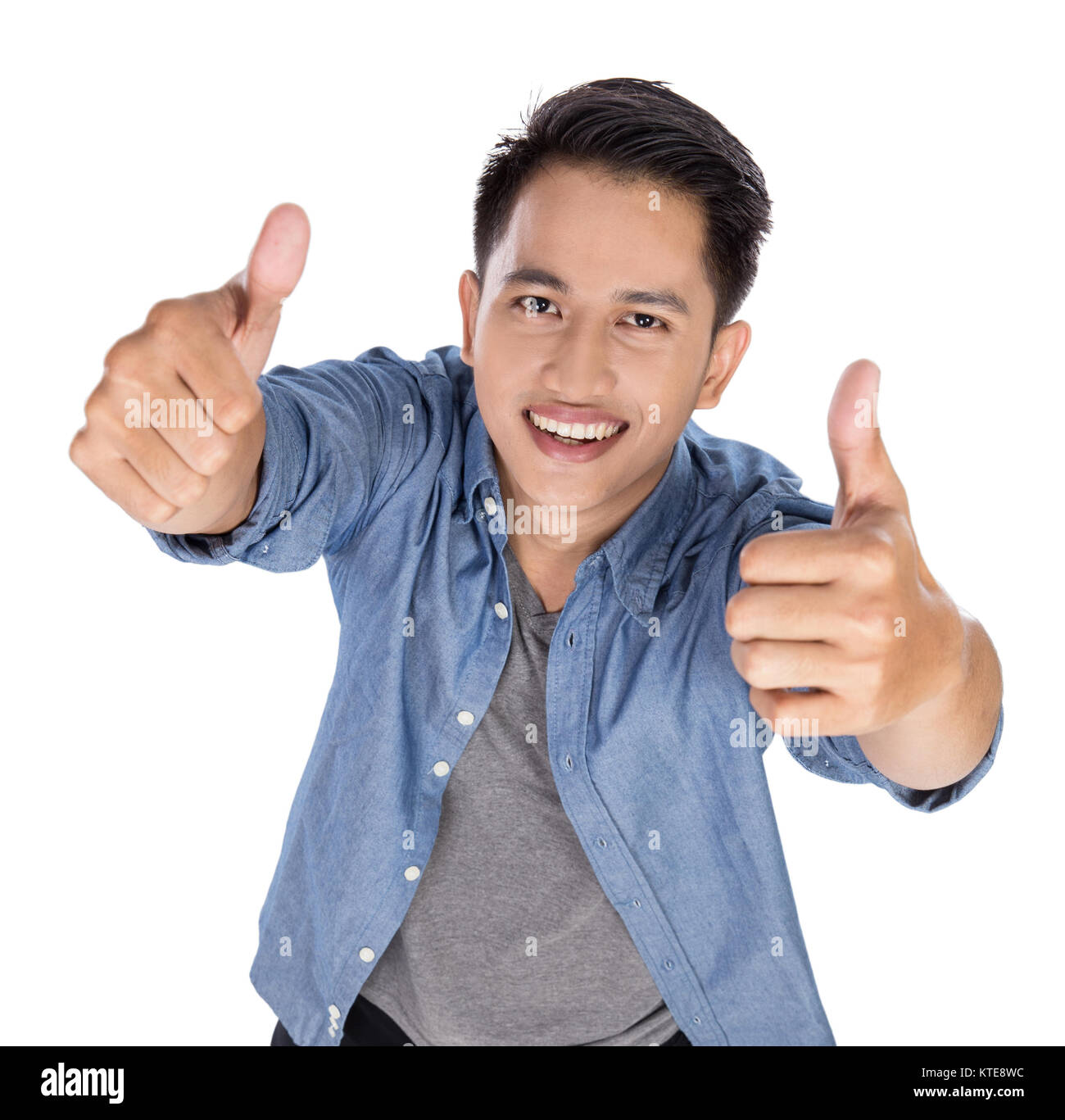 Young asian man posing on the white background, thumbs up