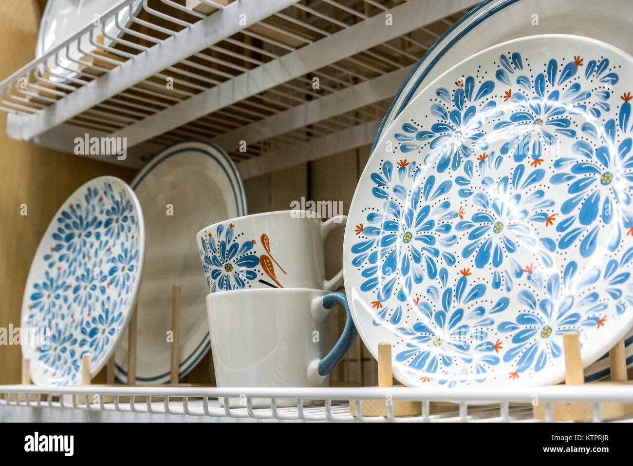 Close up several ceramic plates and cups with blue flower pattern on them standing on kitchen shelf & Close up several ceramic plates and cups with blue flower pattern on ...