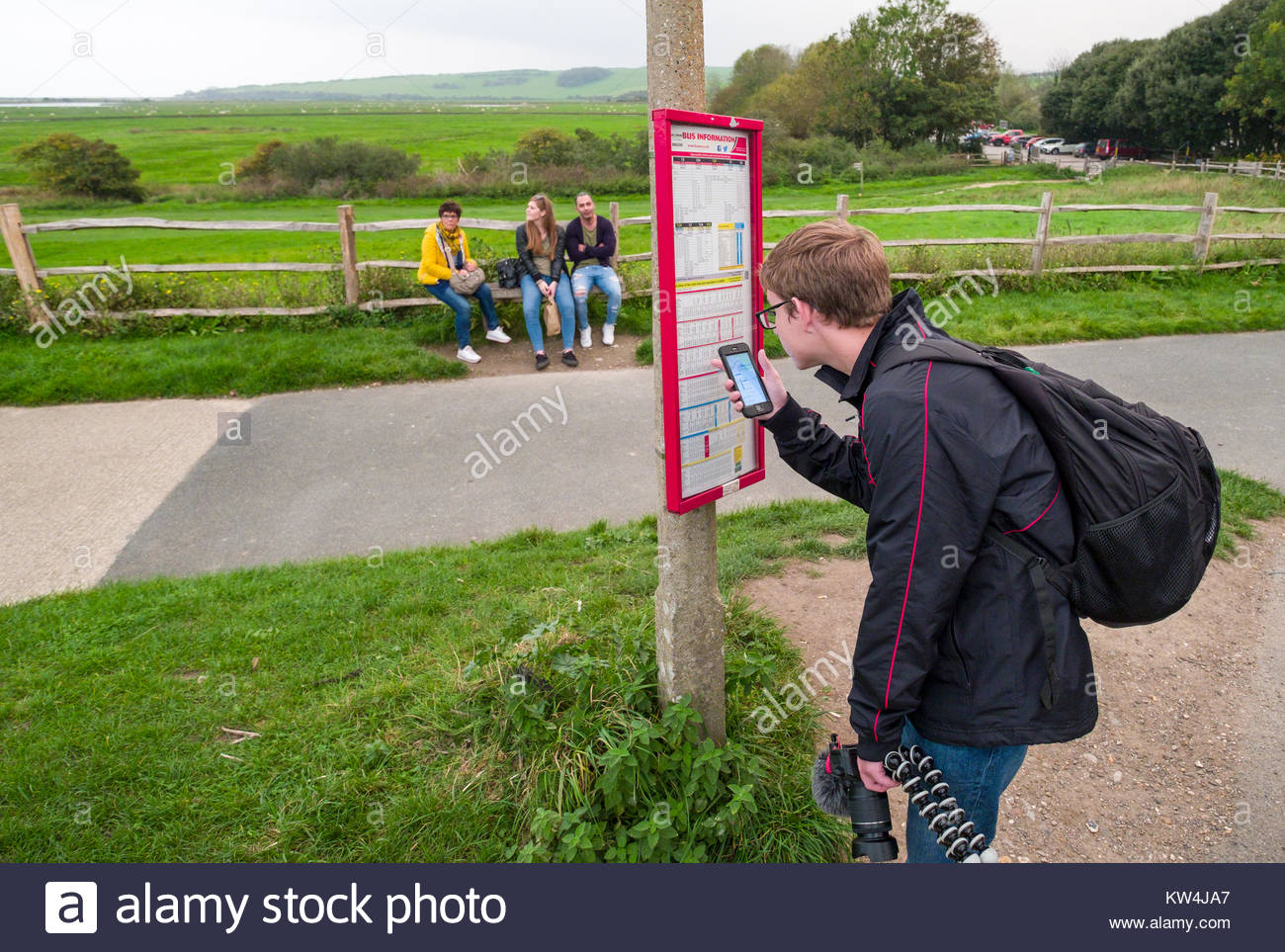 Young Man Checking Bus Schedule On His Smartphone Comparing To Posted Schedule At Bus Stop Exceat Cuckmere Haven Lewes District East Sus Engla