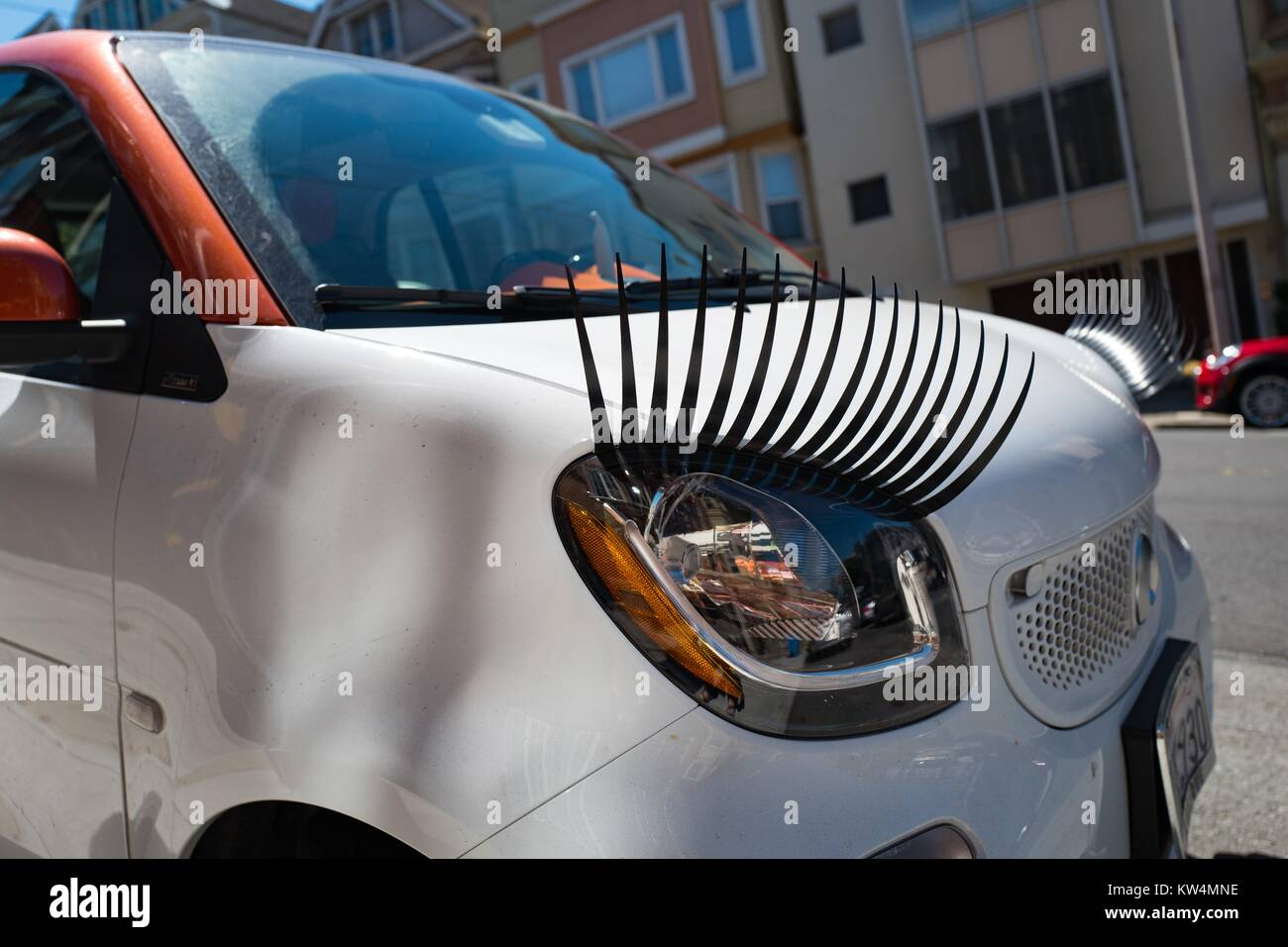 Small Car With Headlights Decorated To Look Like Eyelashes Parked