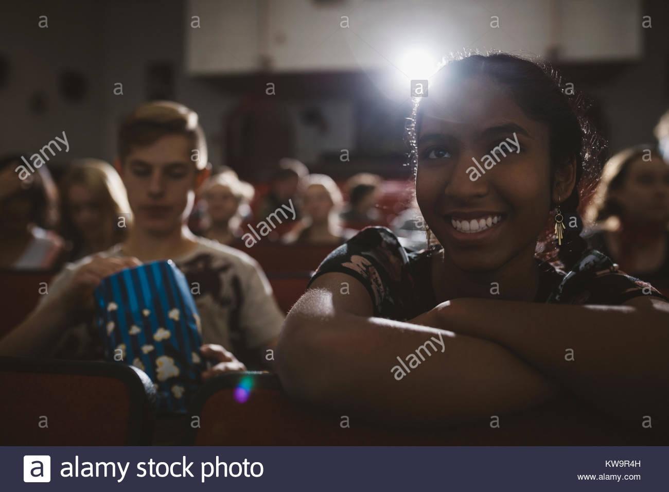 Smiling indian tween girl watching movie in dark movie theater stock smiling indian tween girl watching movie in dark movie theater altavistaventures Images