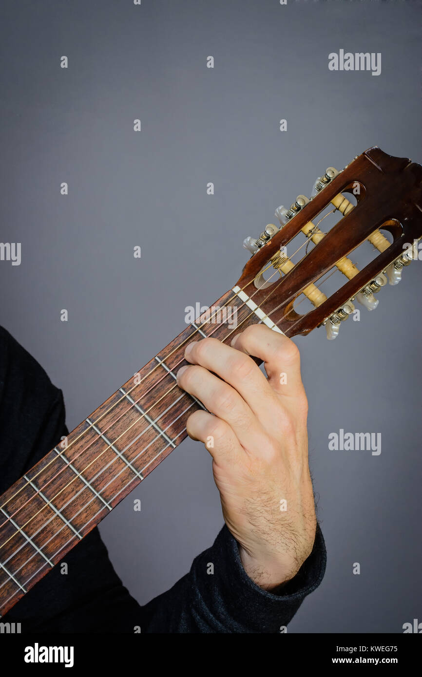 Guitarist Playing E Major Chord On Classical Acoustic Guitar With