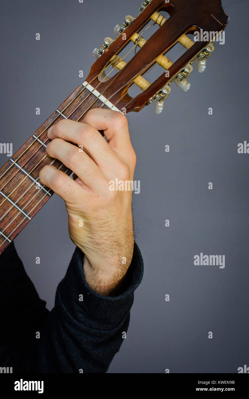 Guitarist Playing An E Major 7 Chord On Classical Acoustic Guitar