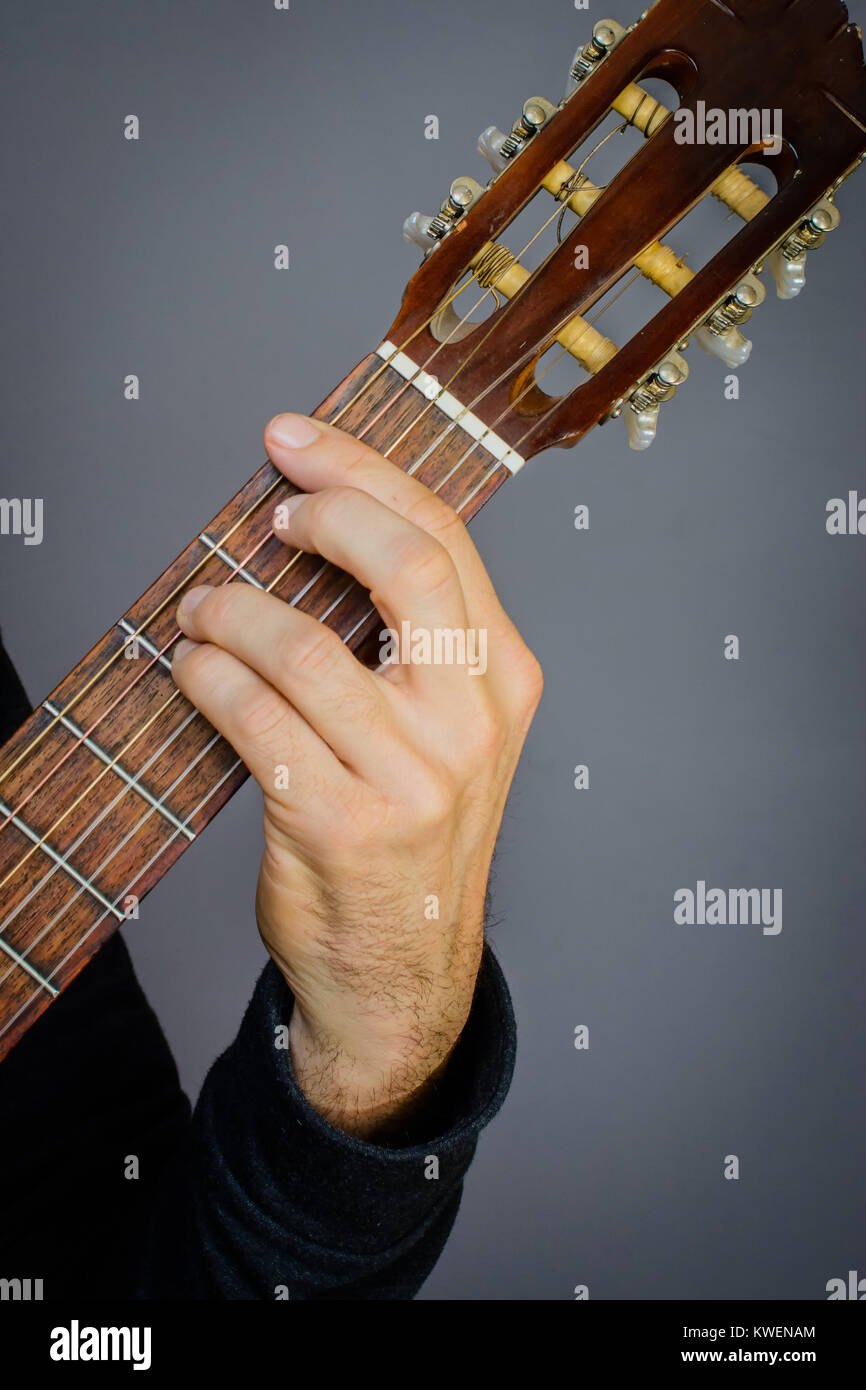 Guitarist Playing An F Minor Chord On Classical Acoustic Guitar With