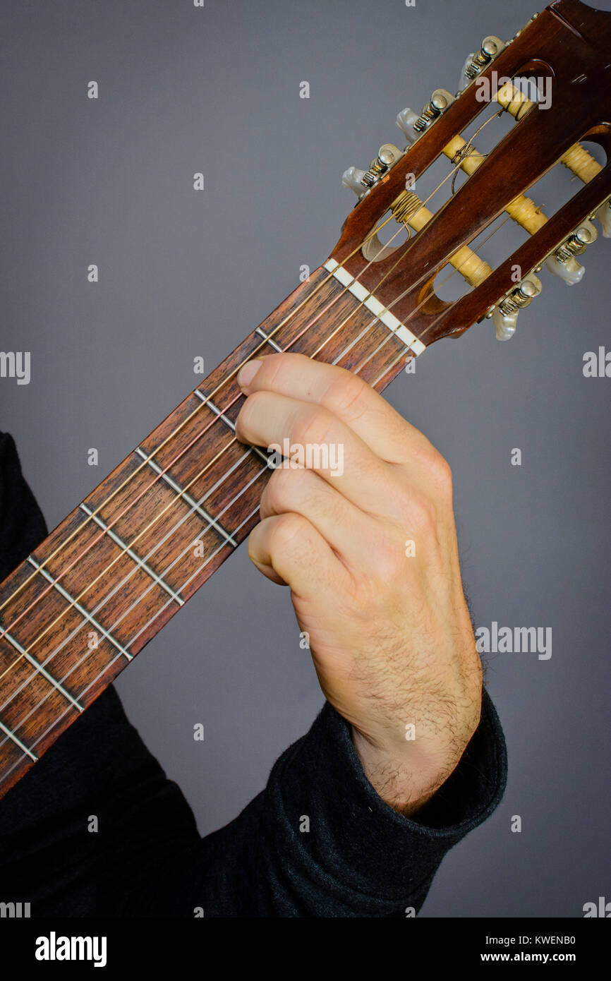 Guitarist Playing An E Minor Chord On Classical Acoustic Guitar With