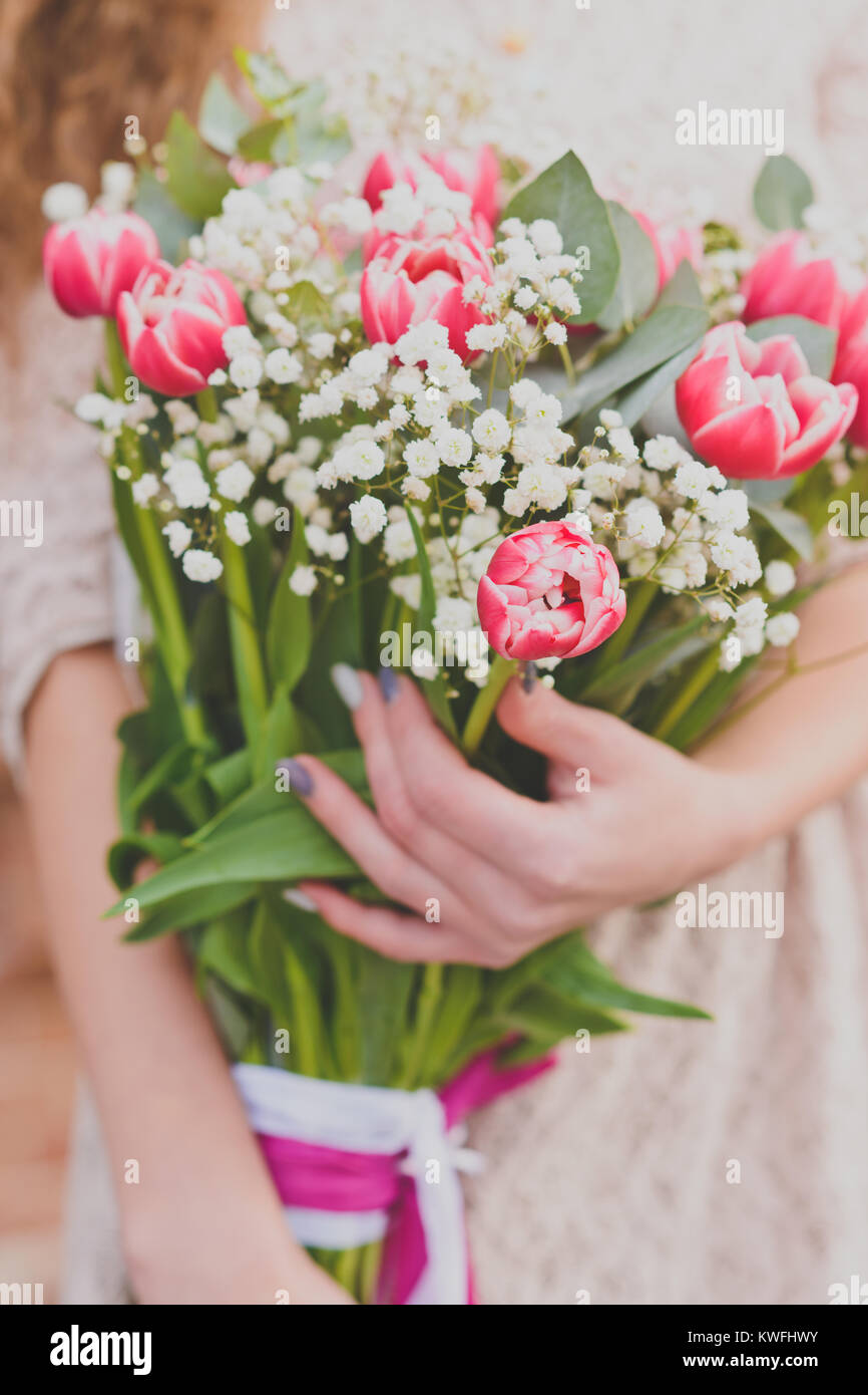 Flower Bouquet Of Red Tulips And Gypsophila In Womans Hands Stock