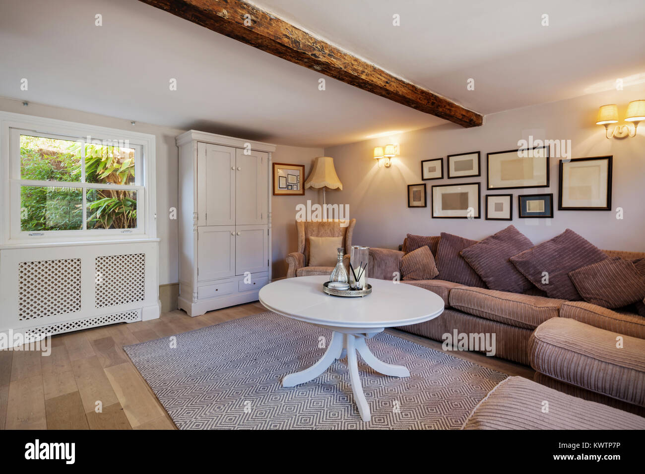 Stylish Cottage Living Room Containing Sofa With Large Cushions, Chic Simple  Decor, Numerous Picture Frames, Coffee Table, Cupboard Window And Exposed