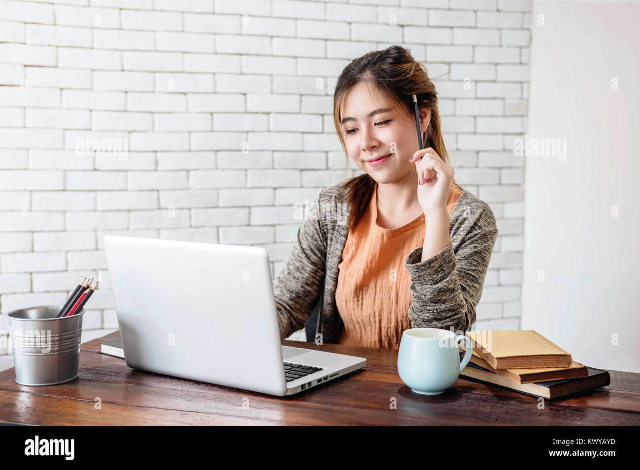 home office work. Young Woman Working On Laptop At Home Office, Work With Happy Smiley Face And Thoughtful Posture, Dressing Casual In Warm Cozy House Office