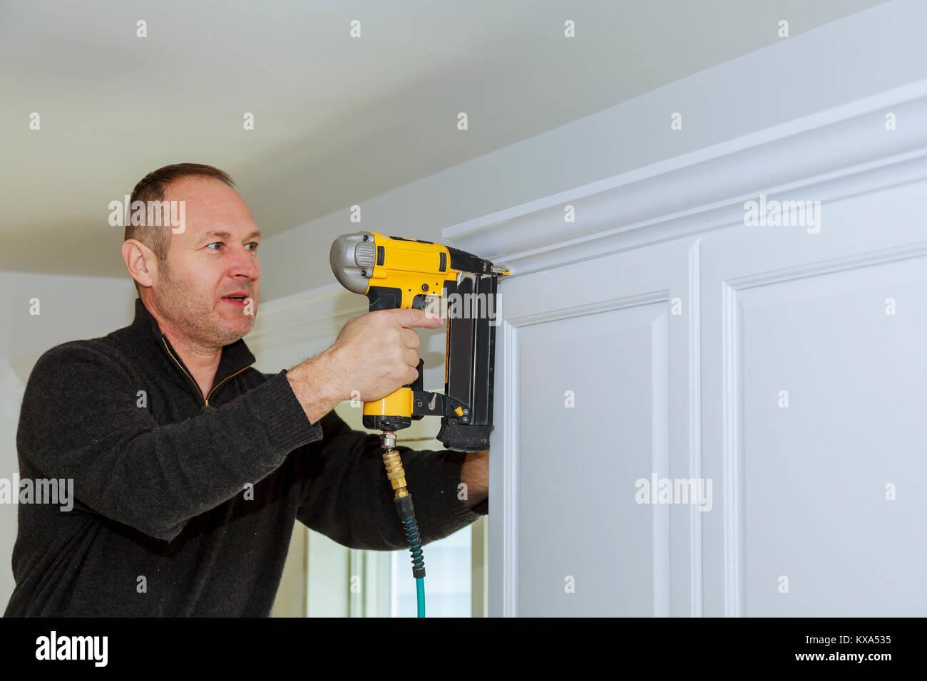 Handyman working using brad nail air gun to Crown Moulding on white ...