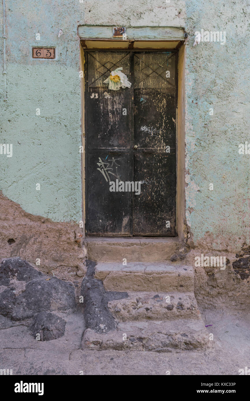 Double black metal doors with a white paper flower posted on the left side stone steps and sidewalk and a light green wall in Guanajuato Mexico & Double black metal doors with a white paper flower posted on the ...