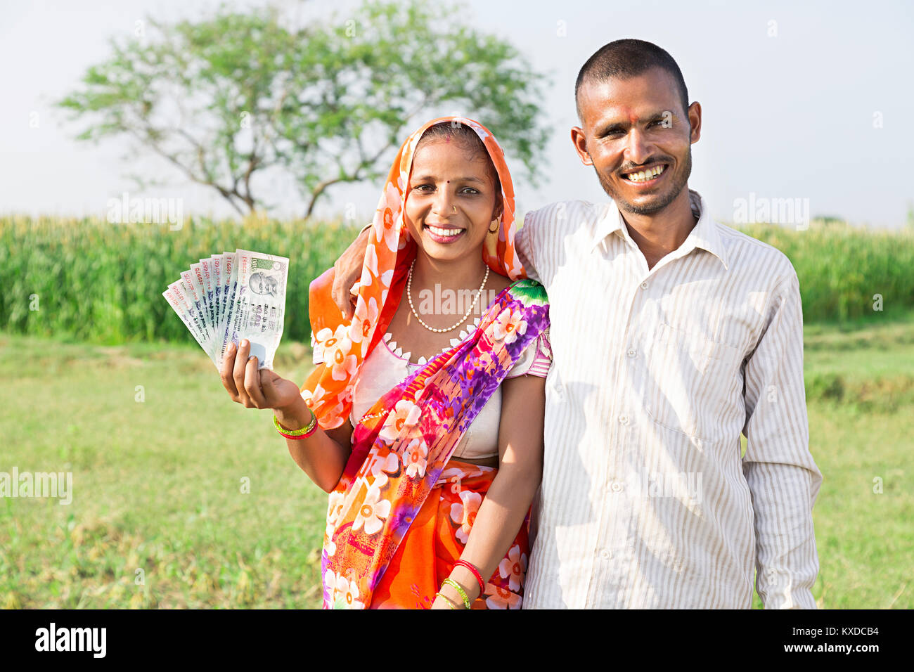 2 indian rural farmer couple showing rupees notes farm village