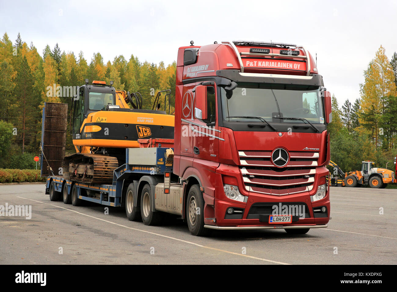 VAAJAKOSKI, FINLAND - SEPTEMBER 22, 2017: Red Mercedes-Benz Actros 2653  semi trailer of P and T Karjalainen Oy is ready to transport a JCB tracked  exc