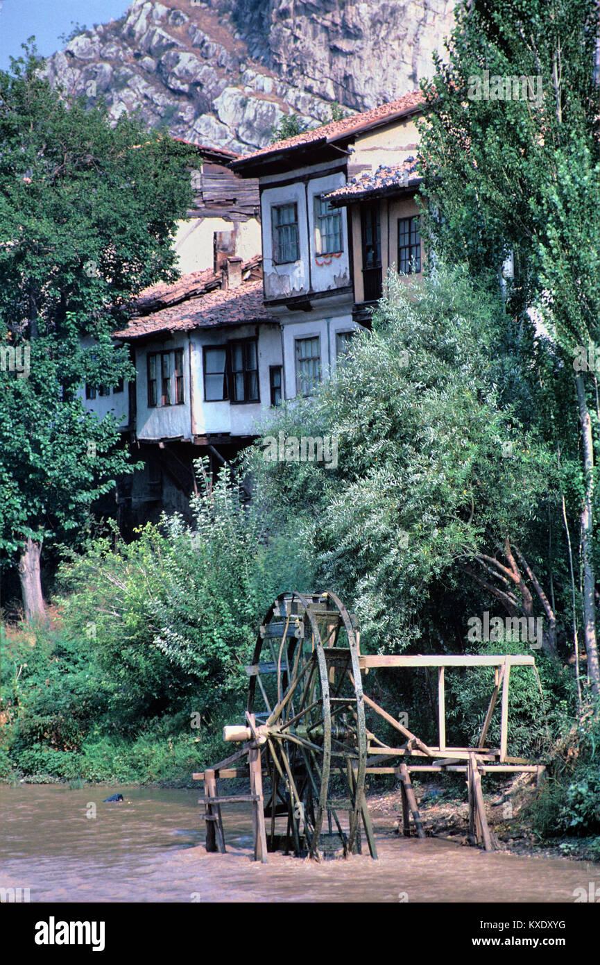 waterwheel on yesilirmak river and riverside wooden ottoman houses